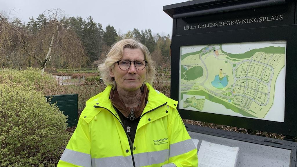 En kvinna i gul reflexjacka står framför en skylt med en karta uppsatt över kyrkogården.