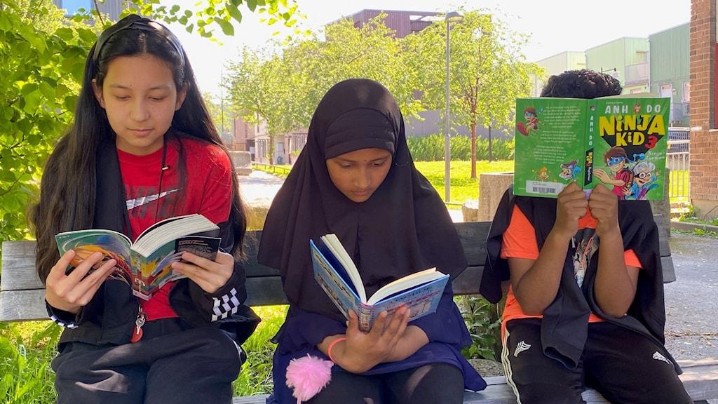 Tre elever från Fittjaskolan som läser böcker.