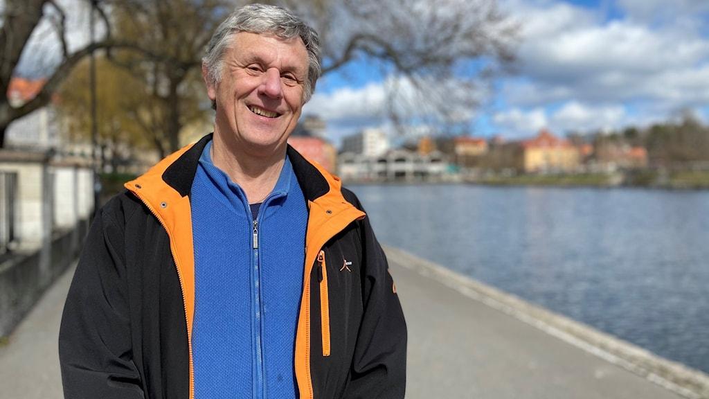 Ola Andersson står och tittar in i kameran med ett leende. Han har en svart vindjacka på sig med orange detaljer vid kragen och en blå kofta under. Han står vid vattnet, vid Maren i Södertälje.