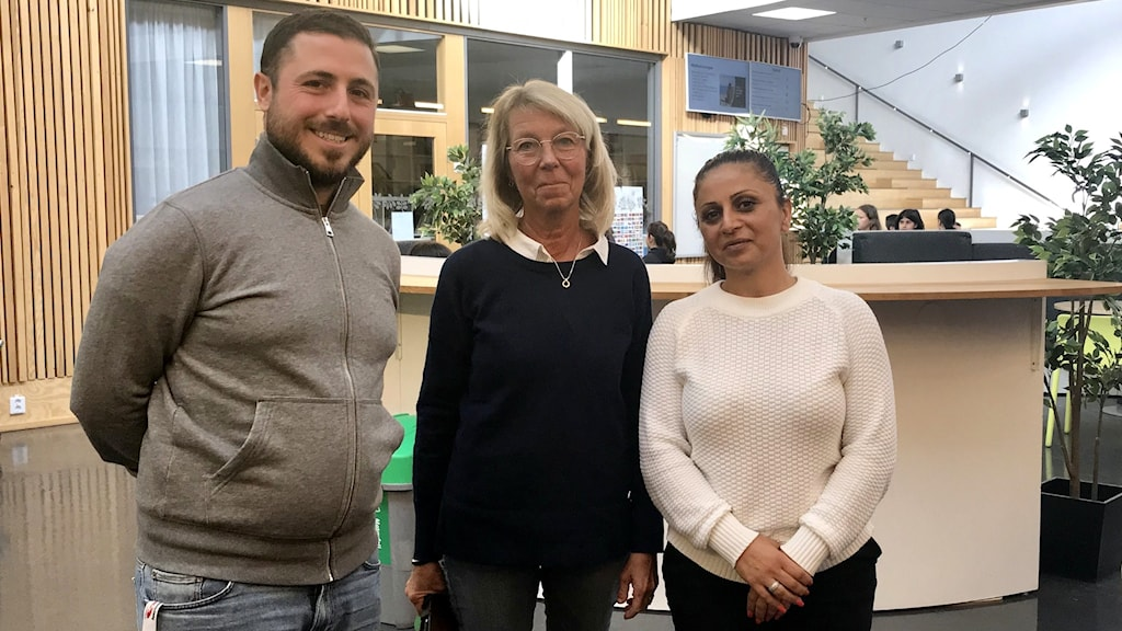 Tre lärare står på skola.