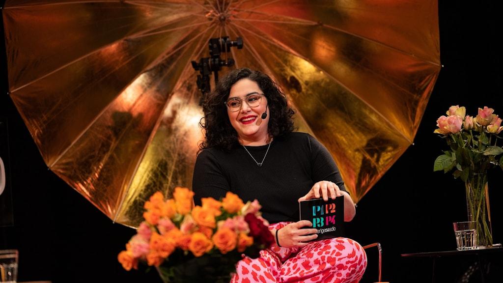 Kvällens värd Tina Mehrafzoon sitter på scenen med blommor framför sig.