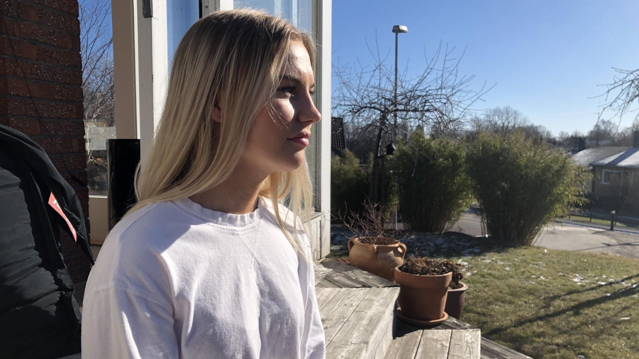 En ung kvinna i profil  i vit tröja blickar ut idet okända