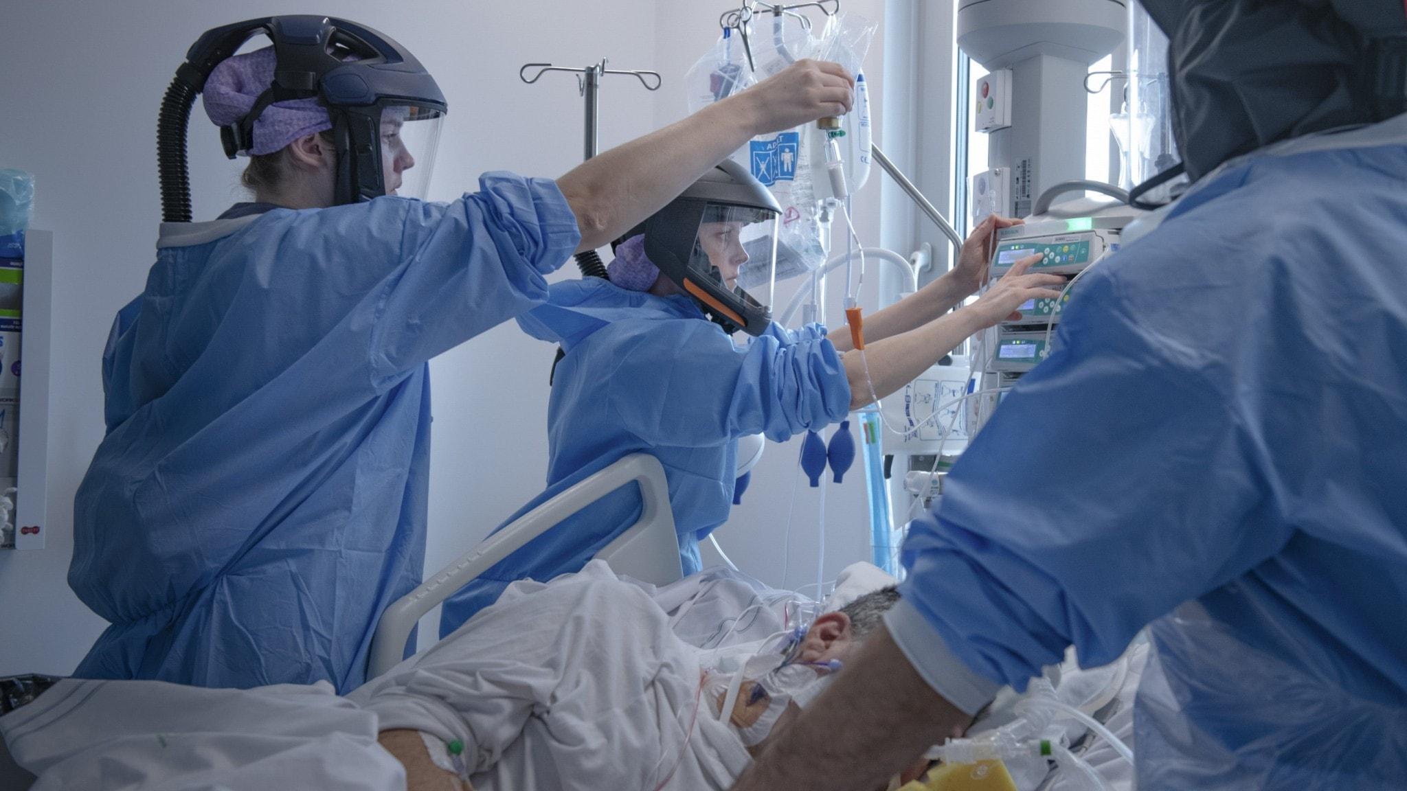 Tre personer i skyddskläder tar hand om en patient på IVA