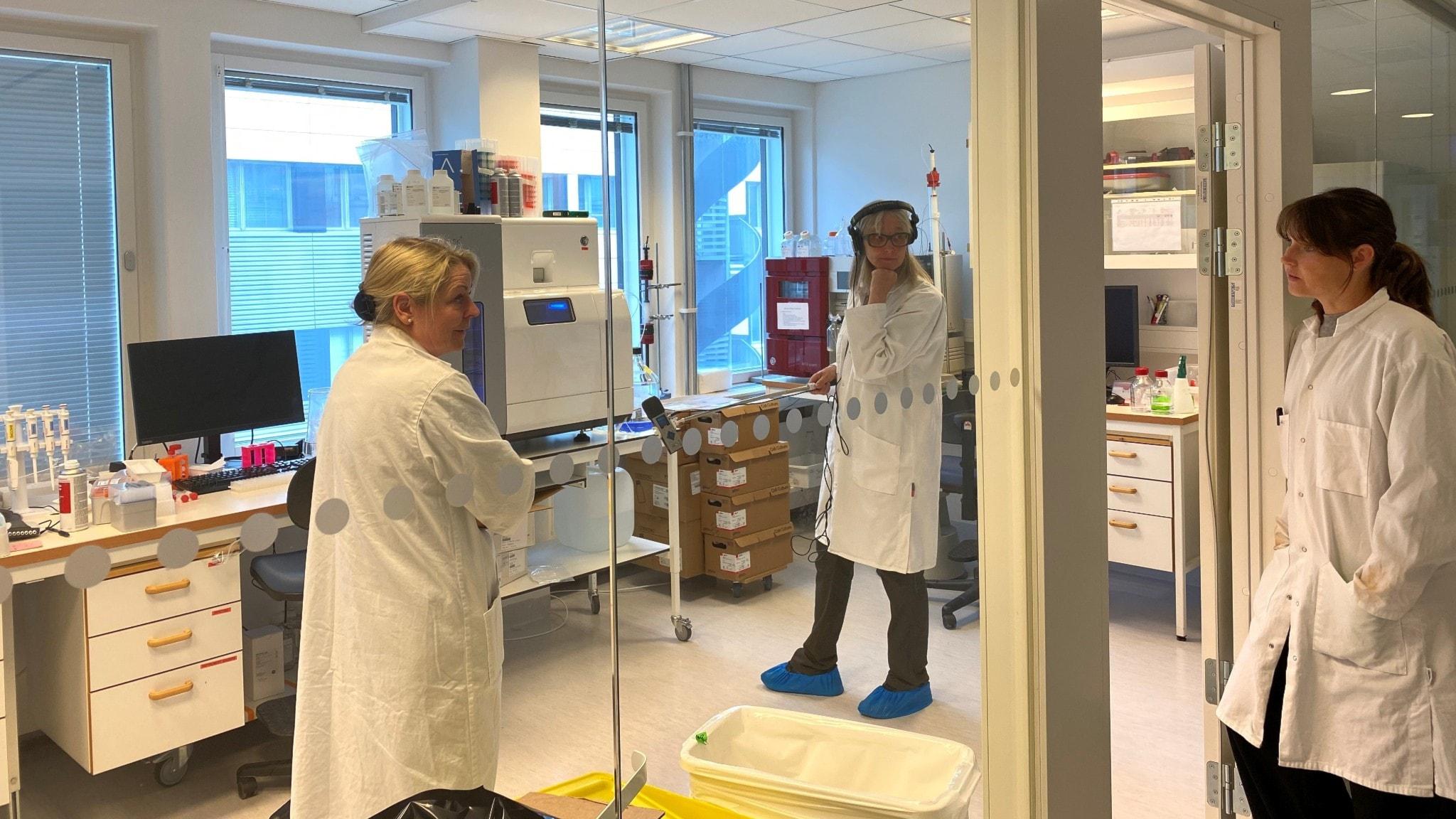 I labbmiljö står tre kvinnor i vita rockar och diskuterar. Man ser allt genom en glasvägg. En står i dörröppningen och de två andra inne i rummet. En av kvinnorna är reporter som spelar in ljud från en maskin.