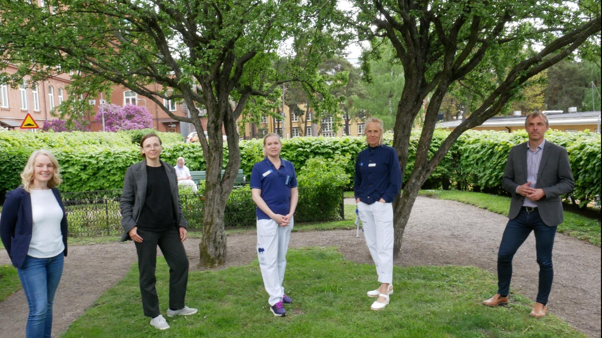 De fem personerna som är med programmet står på coronaavstånd under två träd