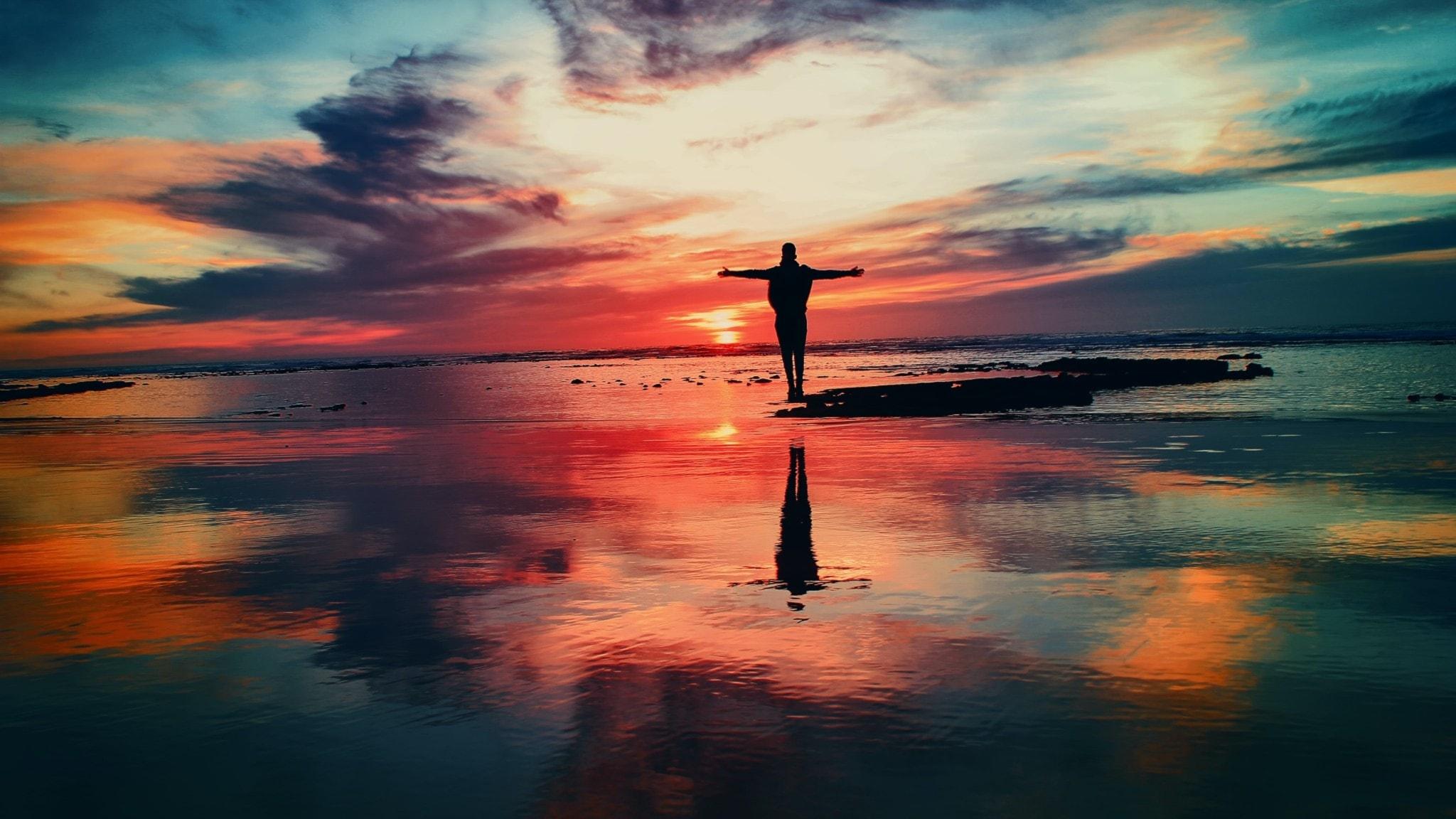 Soluppgång med en person som står på en liten sten ute i grunt vatten