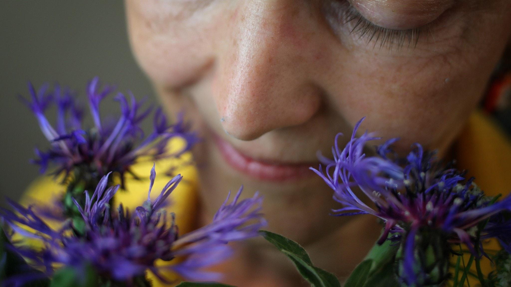 Kvinna luktar på blommor.