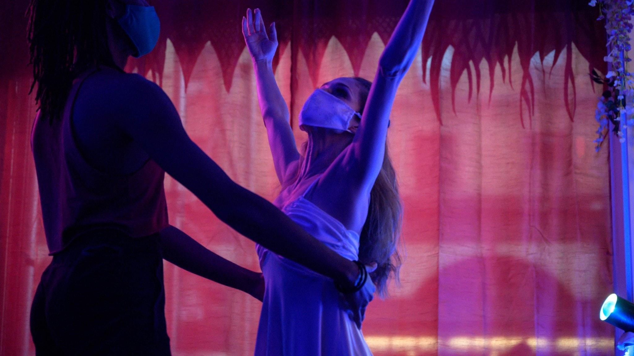 En kvinna iförd munskydd står och sträcker sina bara armar upp i luften, medan en man håller om hennes midja.