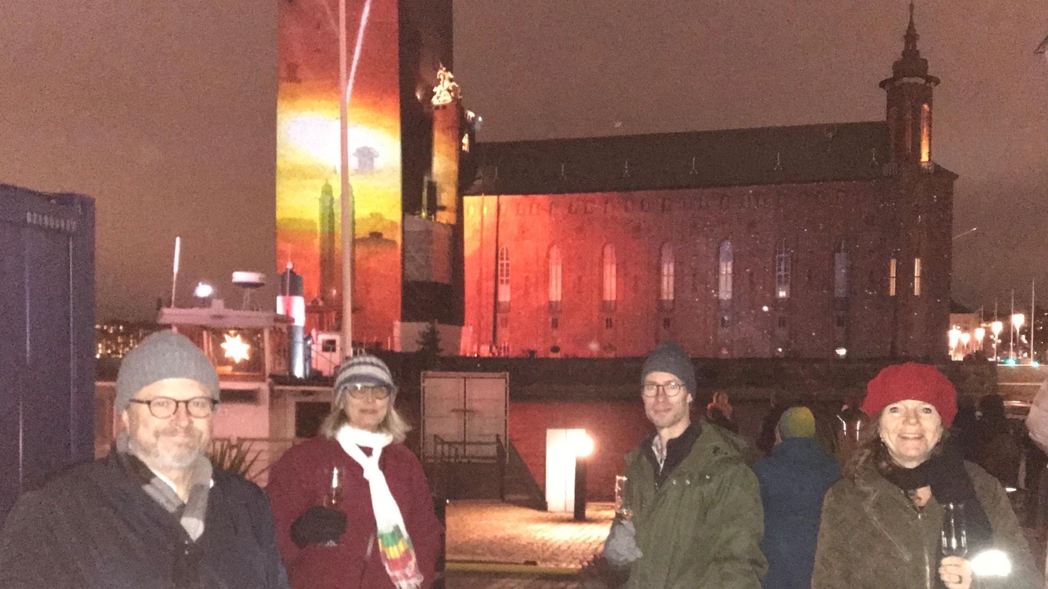 Karsten Thurfjell, Annika Östman, Björn Gunér och Lena Nordlund framför Stockholms stadshus med ljusprojektion av svart hål.