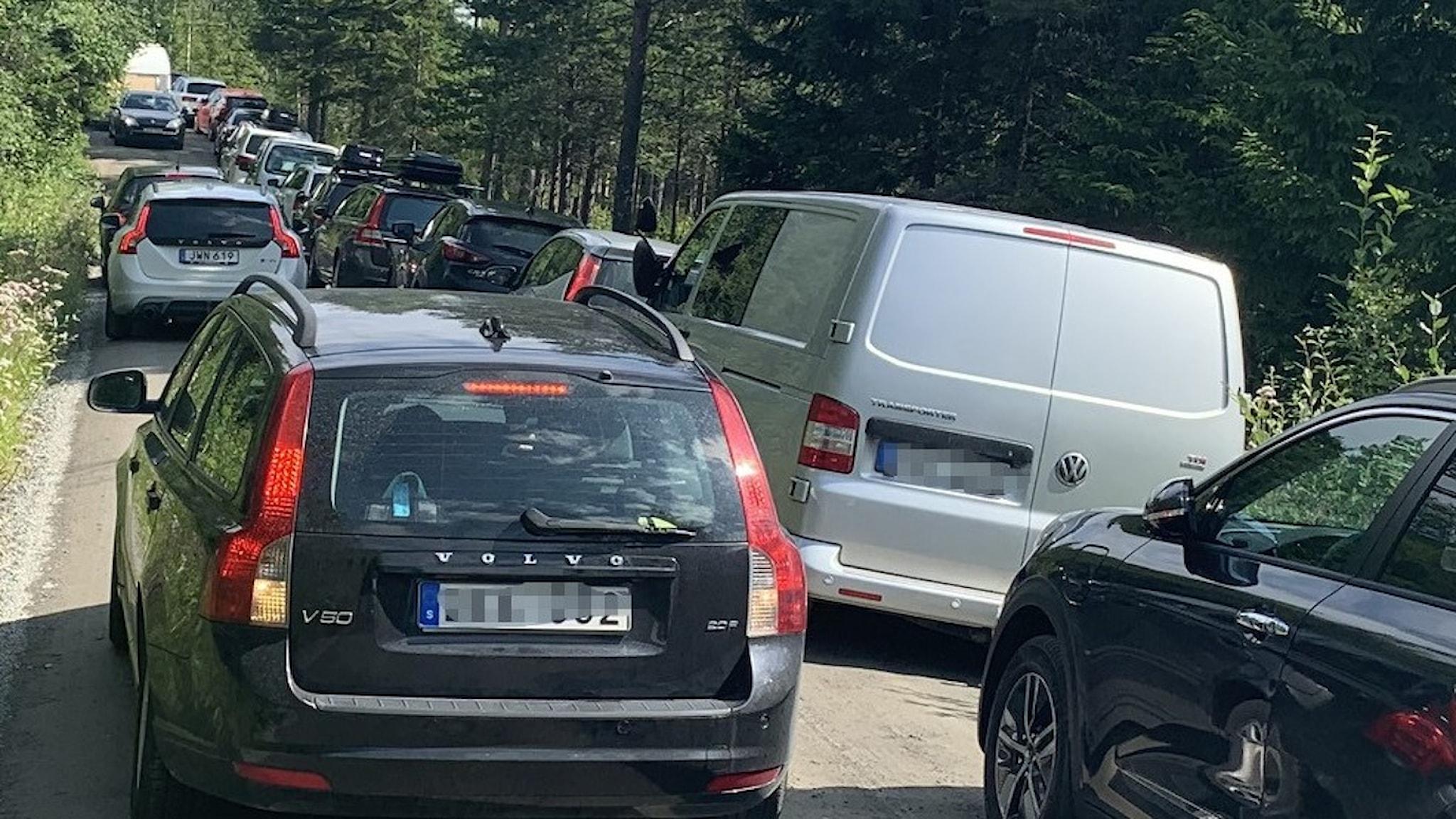 Flera bilar som parkerat trångt längs vägen.