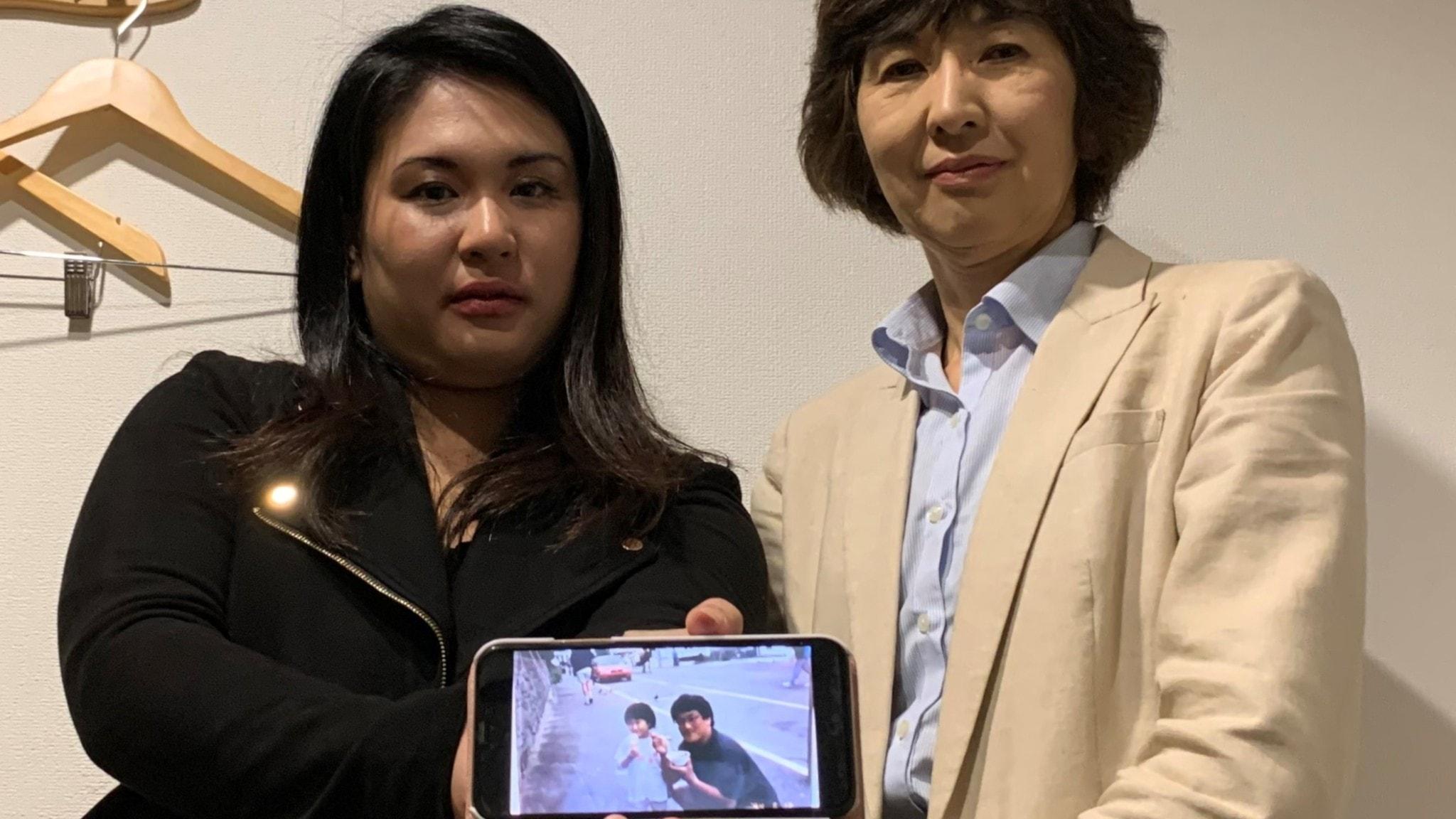 Två japanska kvinnor visar en bild på en pappa och en liten flicka i en mobil