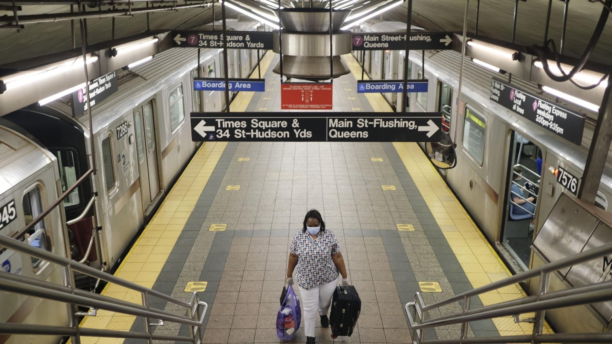 En kvinna går ensam med resväskor på en perrong i New Yorks tunnelbana.