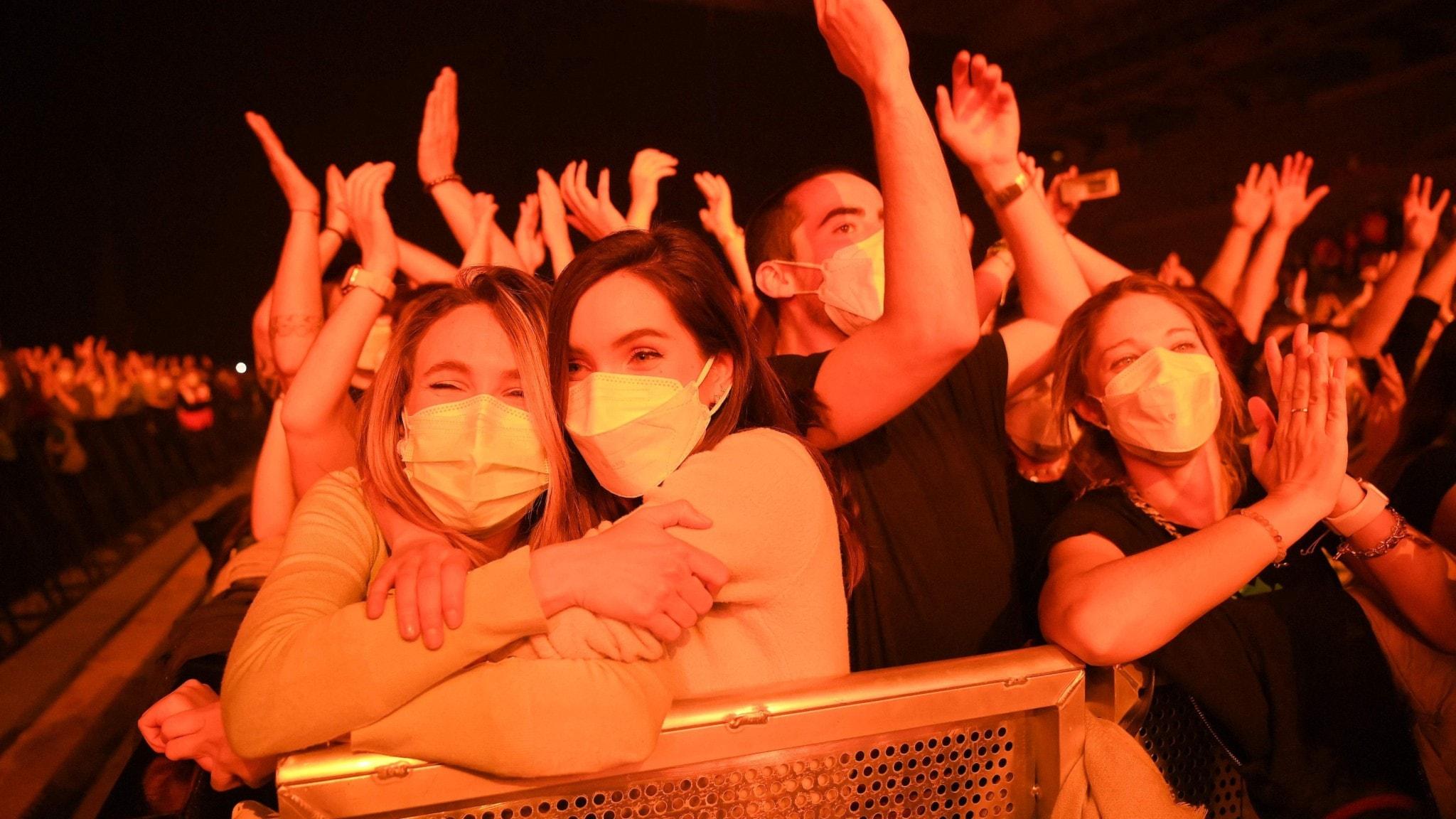 Publik som trängs på konsert i Barcelona, med ansiktsmask på.