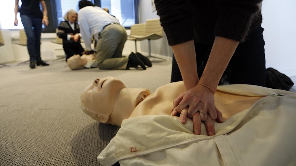 Närbild på en person som tränar hjärt- och lungräddning på en övningsdocka.