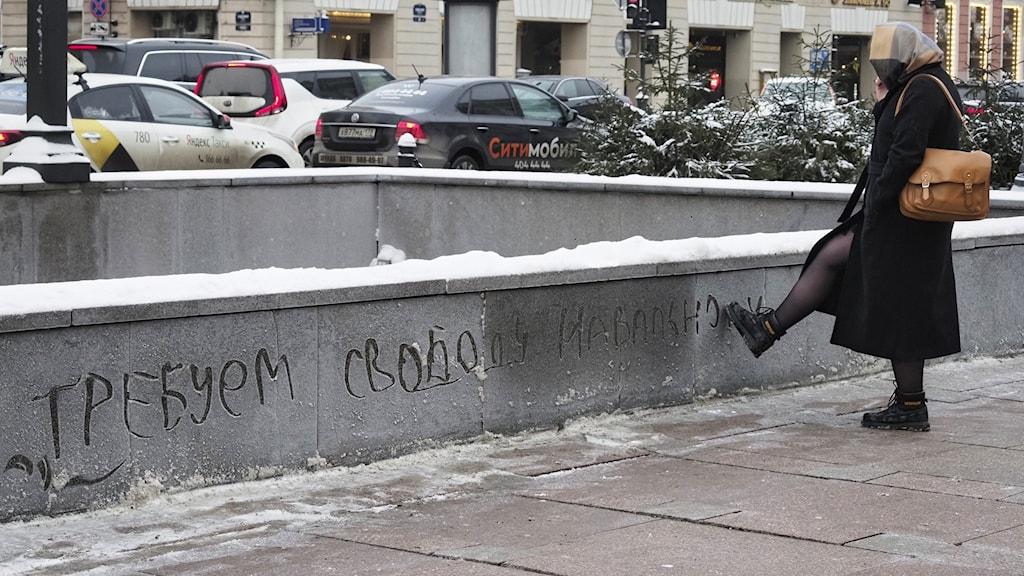 """Kvinna drar med foten över mur där någon klottrat """"vi kräver frihet för Navalnyj"""". Bilden är tagen den 18 januari i St. Petersburg."""