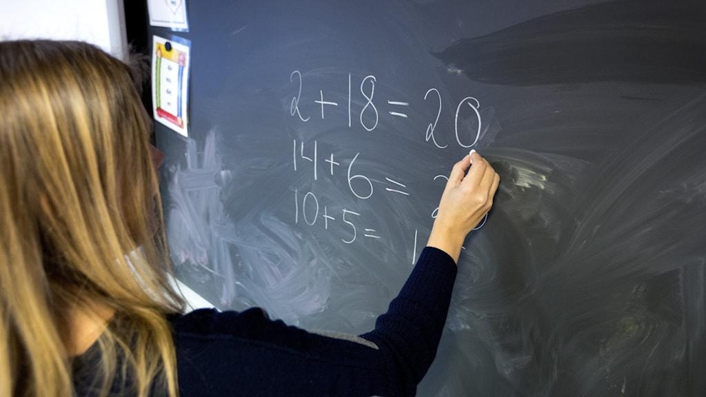 Lärare skriver siffror på svarta tavlan.