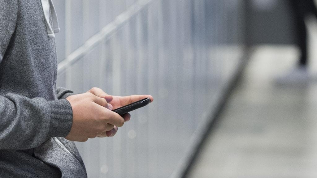En person i skolmiljö som håller i sin mobil.
