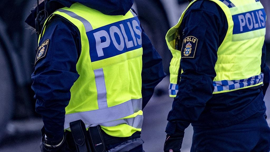 Bild på två poliser med reflexväst där det står polis.