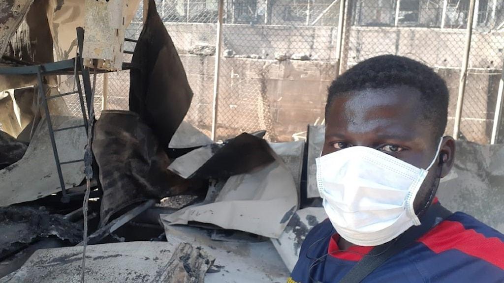 Christian står framför hans nedbrända barack där han bott. Han har munskydd på, bilden är en selfie.