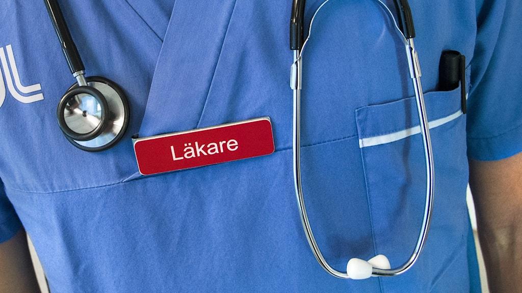 """En överkropp i sjukhuskläder. Runt personens hals hänger ett stetoskop och personen har en skylt som det står """"läkare"""" på."""