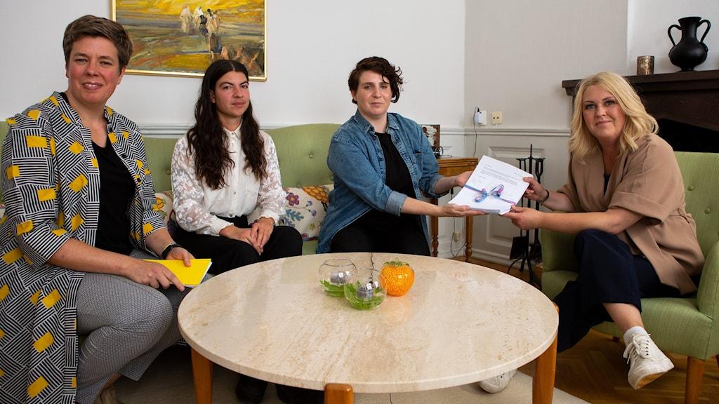 Fyra personer sitter i en soffgrupp, det är RFSLs medlemmar och Lena hallengren. Lena får ta emot namnunderskrifterna.