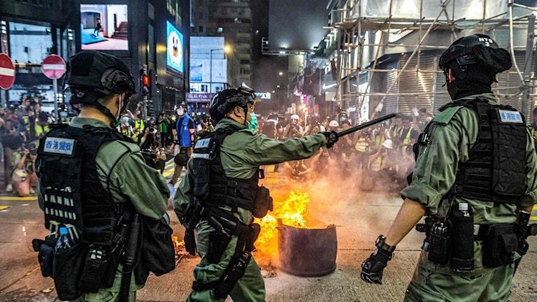 Poliser framför brinnande föremål på gatan i Honkong under protester mot kontroversiell säkerhetslag.