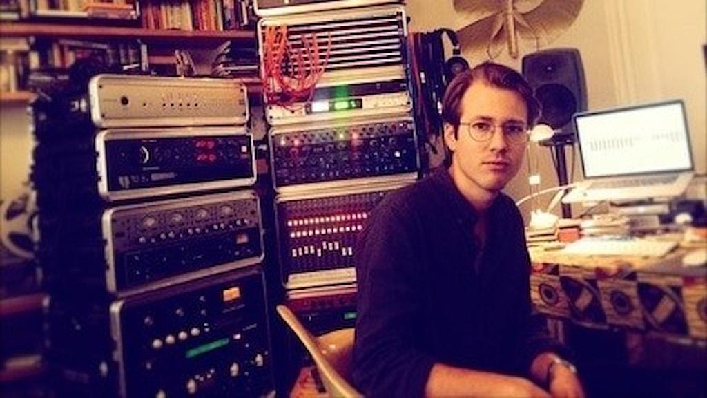 Sebastian Bergström sitter framför ett skrivbord med mixerbord och dator på. Han är omgiven av olika elektroniska musikapparater och böcker.