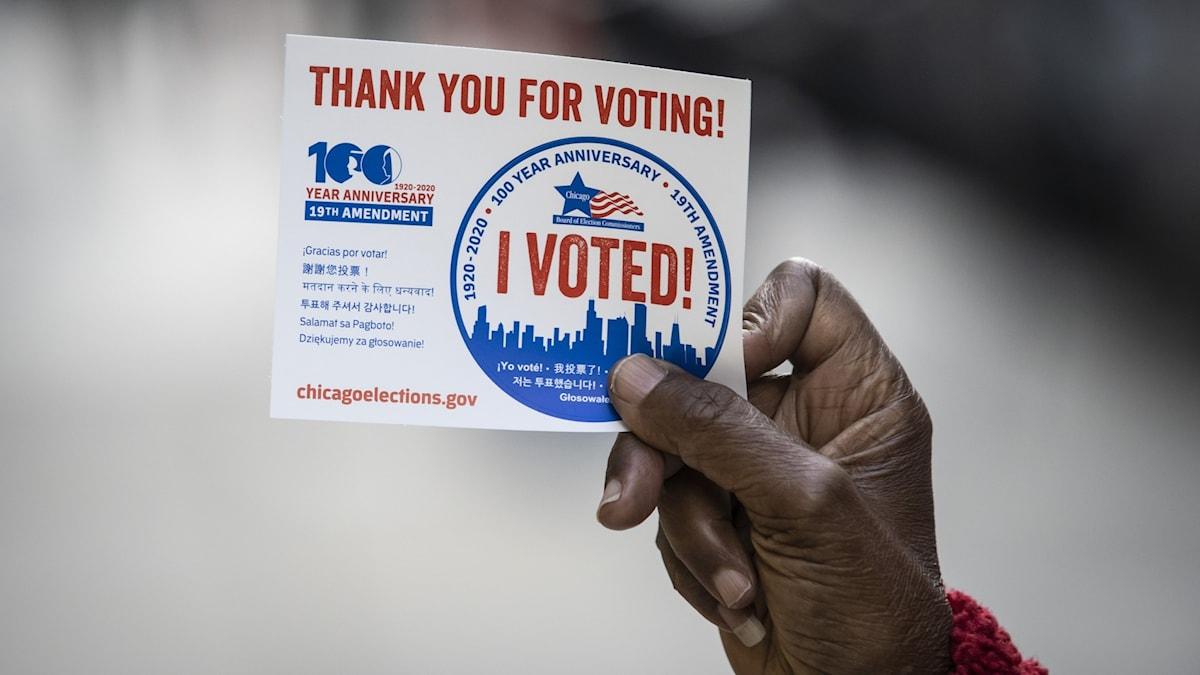 """Hand håller upp en lapp där det står """"Tack för att du röstar"""" på engelska."""