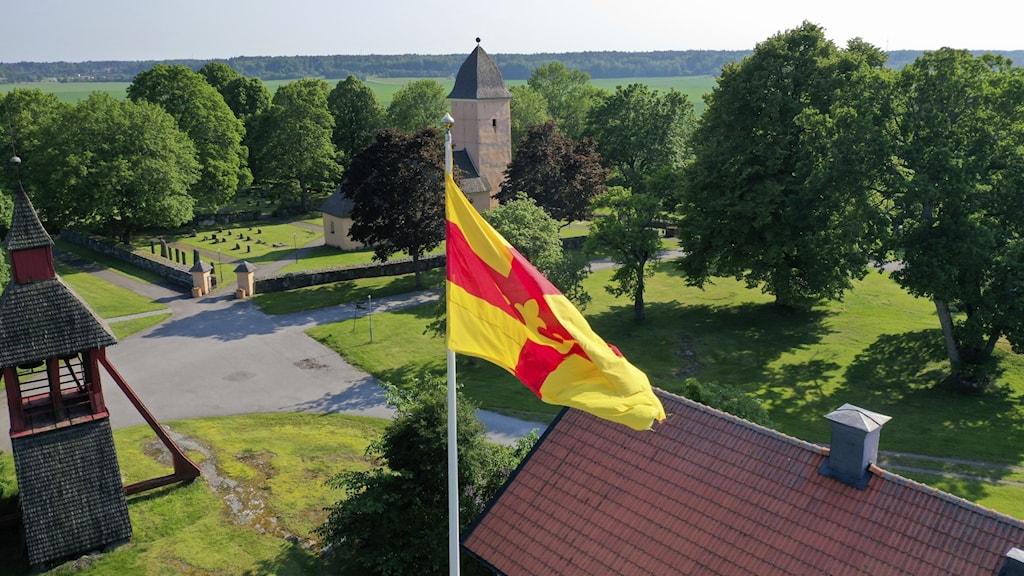 Svenska Kyrkans flagga vajar utanför en kyrka i Uppland.