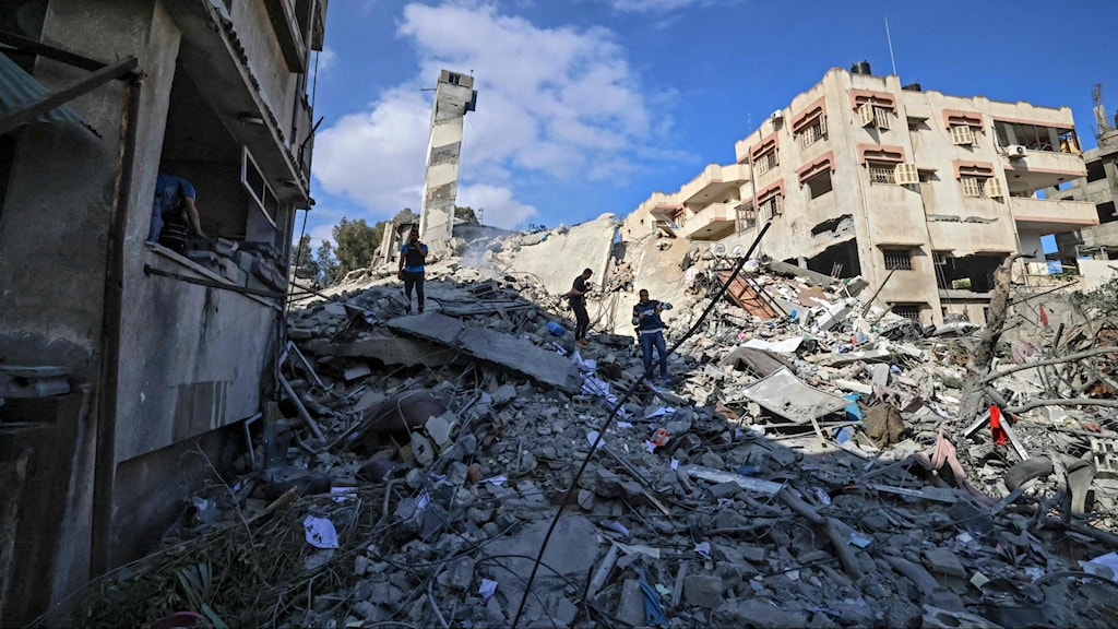 Människor letar i rasmassor från ett hus som förstördes under flygbombningar från Israel.