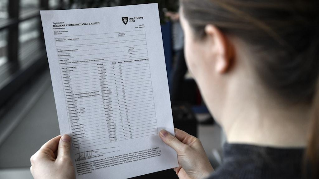 Bild på sittande kvinna som håller ett betygsdokument.
