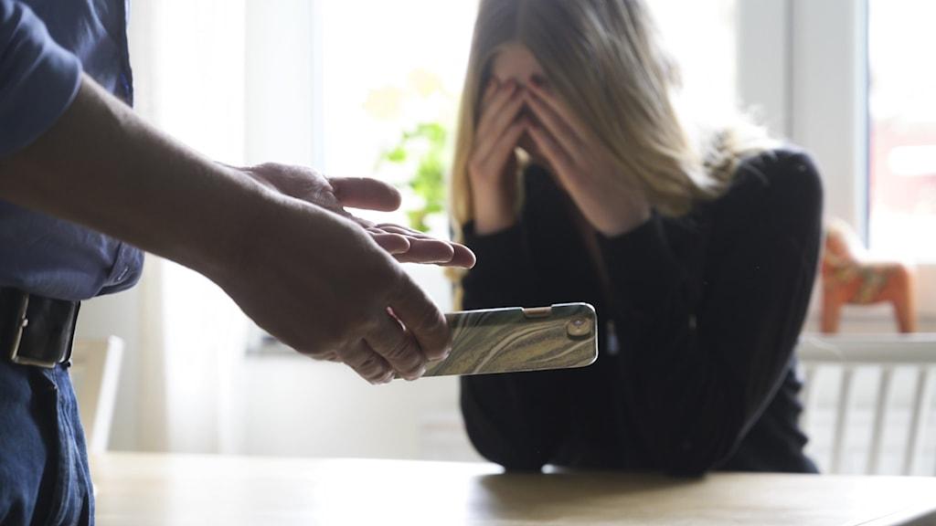 En man som kollar igenom en kvinnas mobil och en kvinna som sitter gråtandes vid köksbordet.