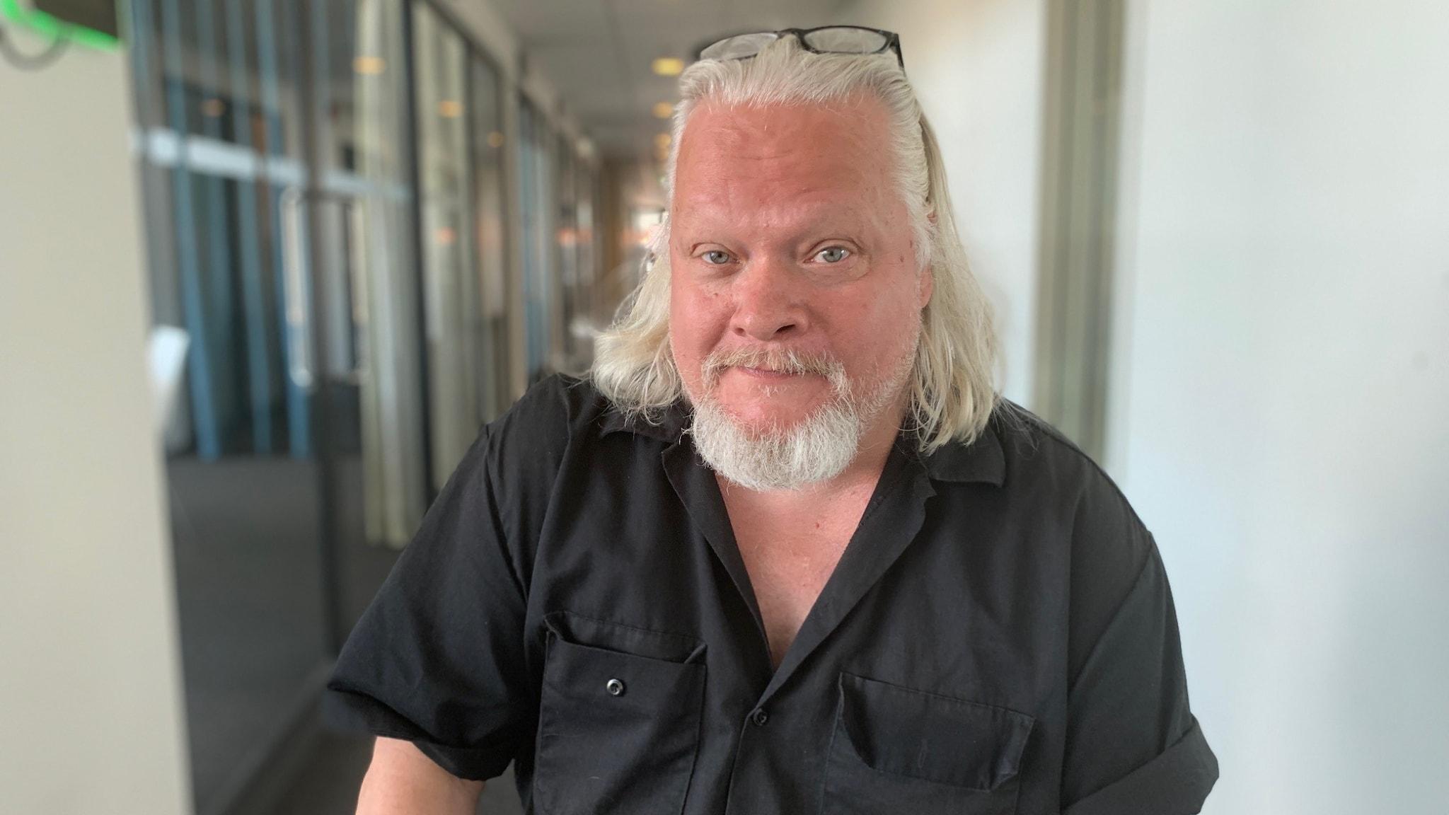 Skådespelaren Kjell Wilhelmsen sitter på en stol och tittar in mot kameran. Han har på sig en svart skjorta och glasögonen på huvudet.