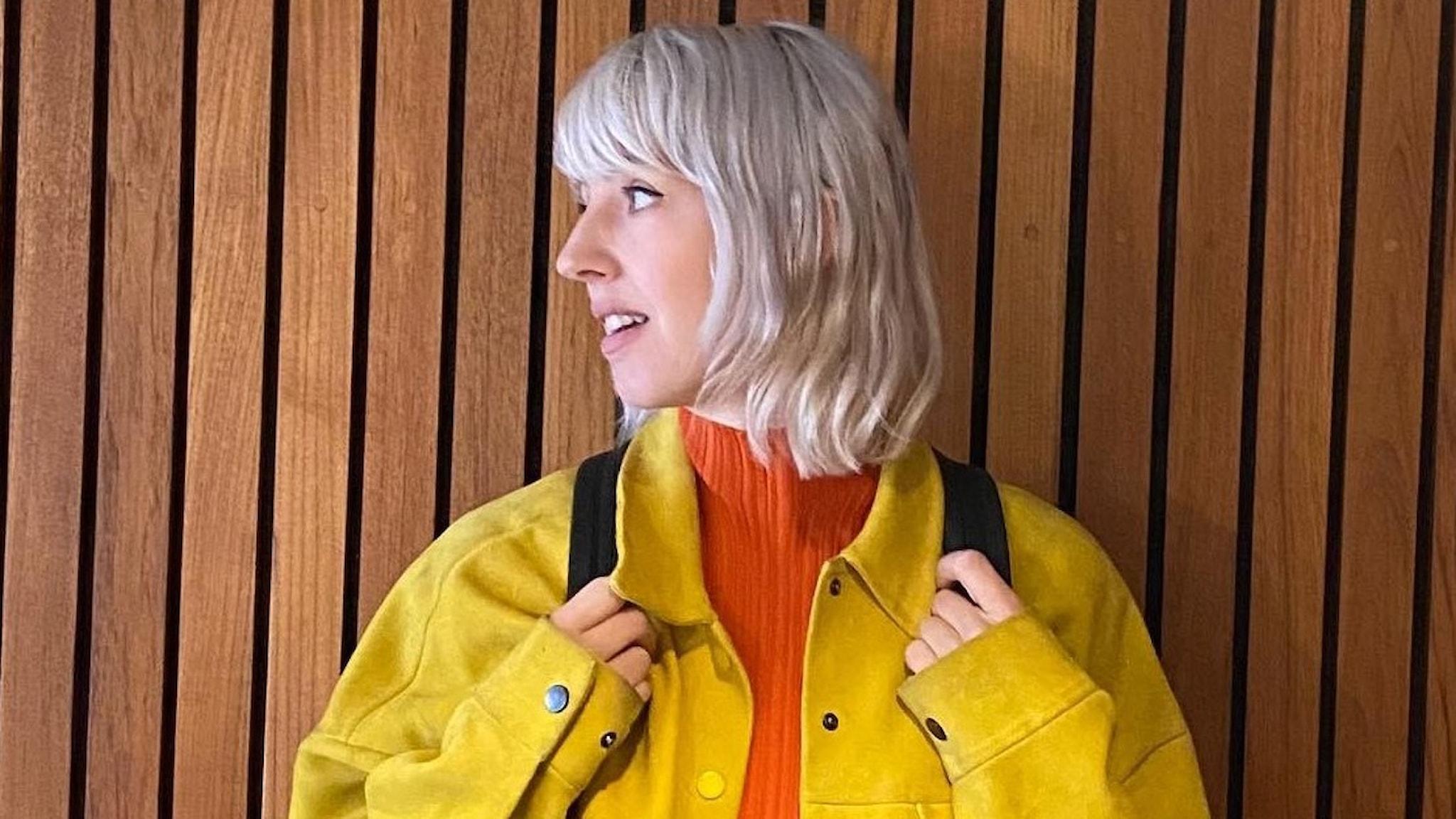 Artisten Veronica Maggio i färgstarka kläder intill en trävägg.