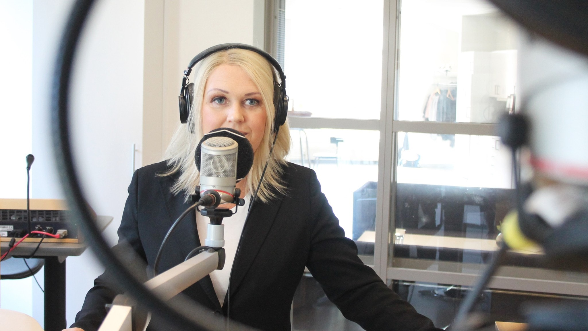 Kvinna vid mikrofon i radiostudio.
