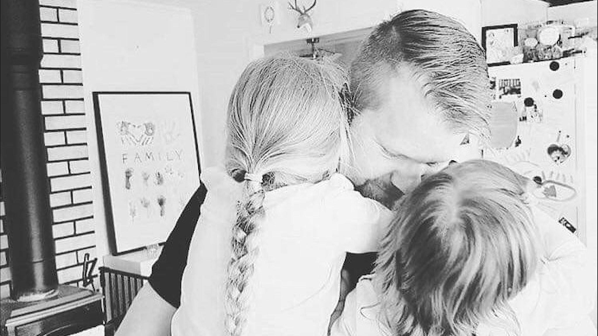 Svartvit bild av Tom tillsammans med två barn.