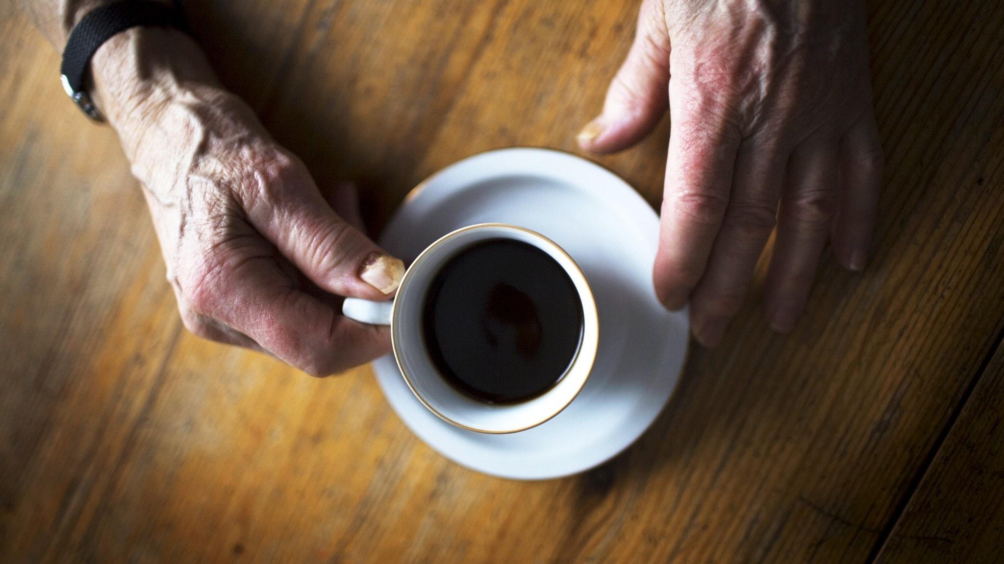 Äldre person dricker kaffe. Närbild på händer och kaffekopp.