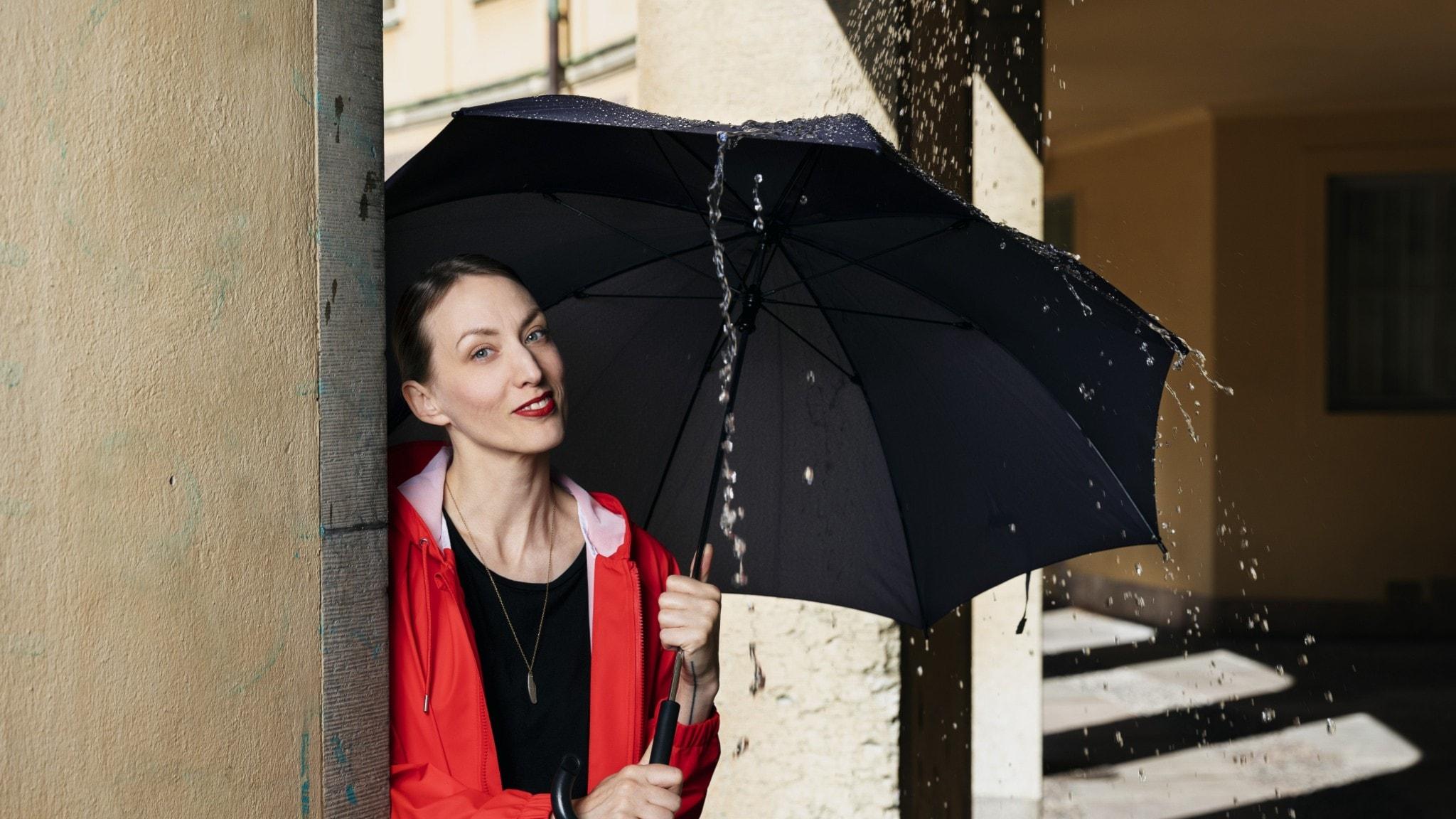 Cecilia Düringer, programledare Historiska väder, står iförd röd regnrock och ett paraply på en solig innergård – men det regnar på paraplyet just där Cecilia står.