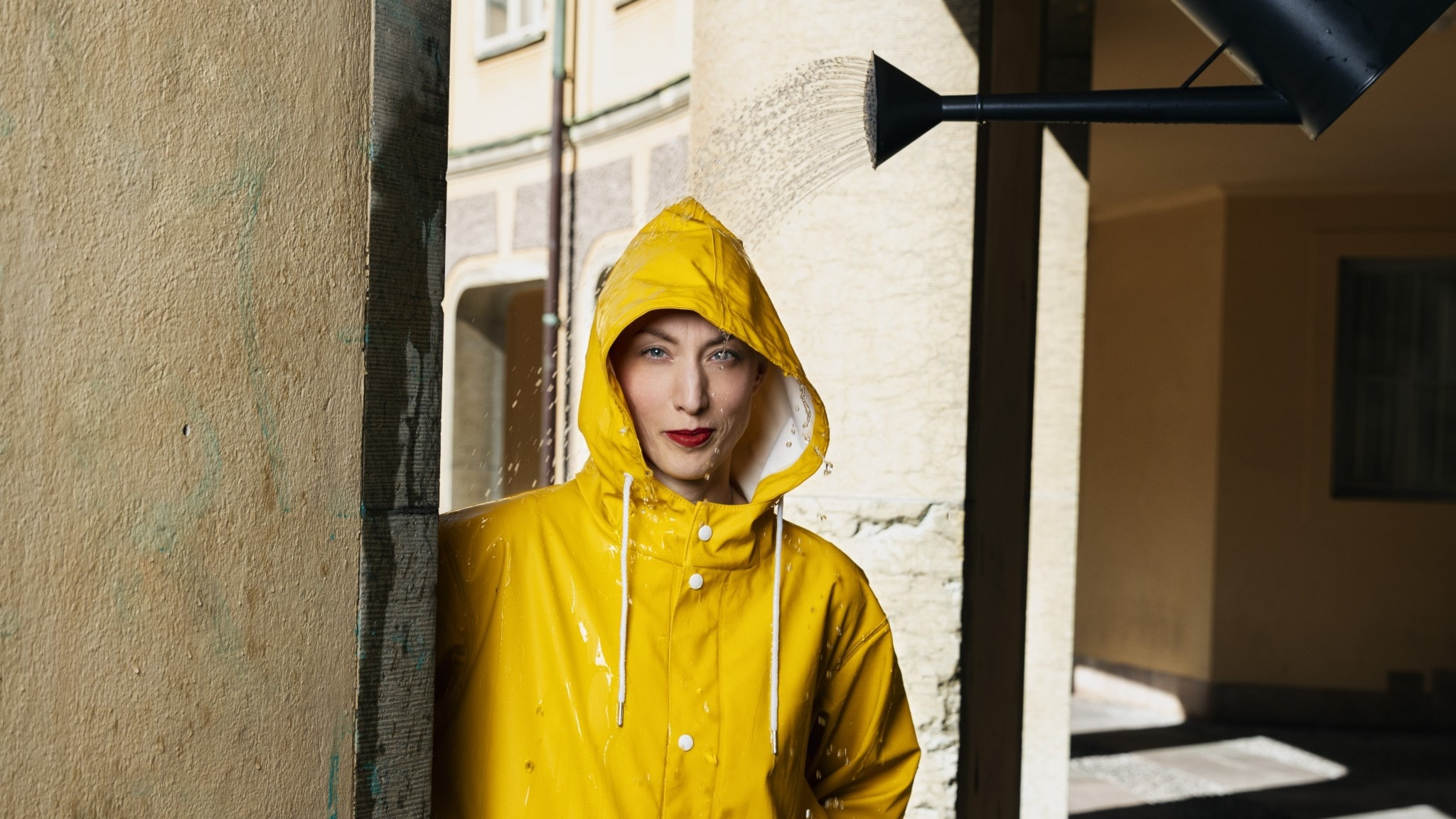 Cecilia Düringer, programledare Historiska väder i P1, står iförd gul regnrock en solig dag. I höger hörn syns en vattenkanna och ur den kommer vatten rakt ner över Cecilia.