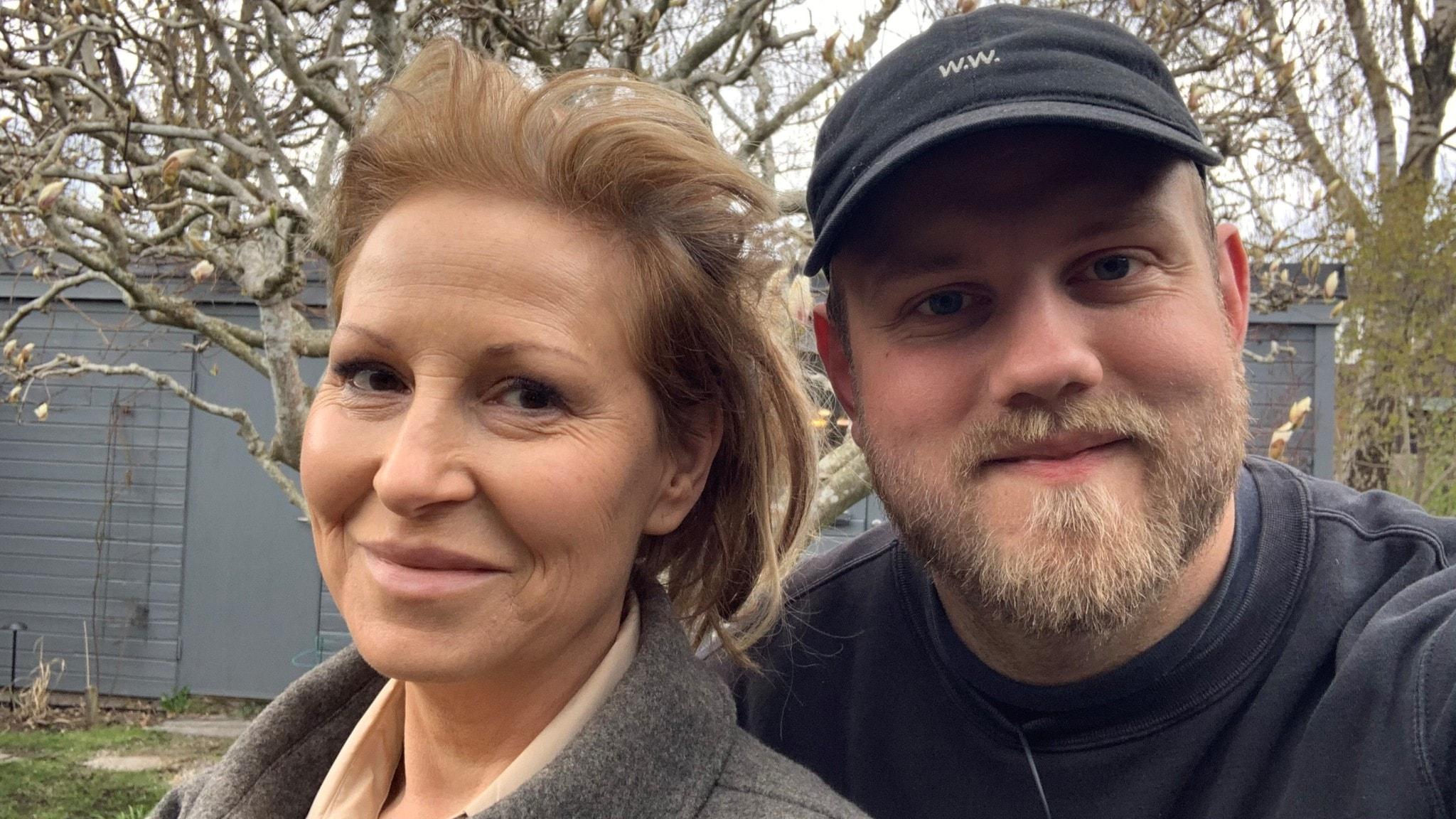 Närbild på Anna Mannheimer och Hector Apelgren. De står utomhus med en magnolia i bakgrunden.