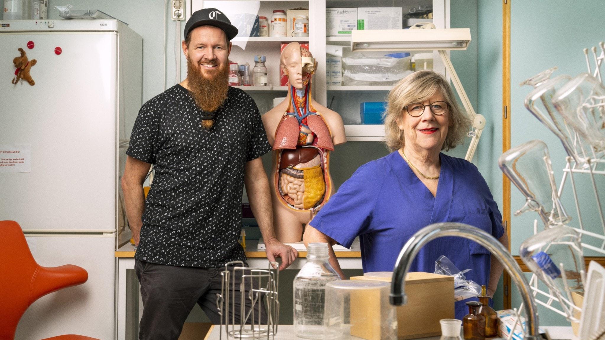 Två personer ståendes i ett laboratorium, man med skägg och keps till vänster i bild, till höger om honom en anatomisk modell över en människokropp. I förgrunden, till höger, står en kvinna med blå läkarskjorta och glasögon.