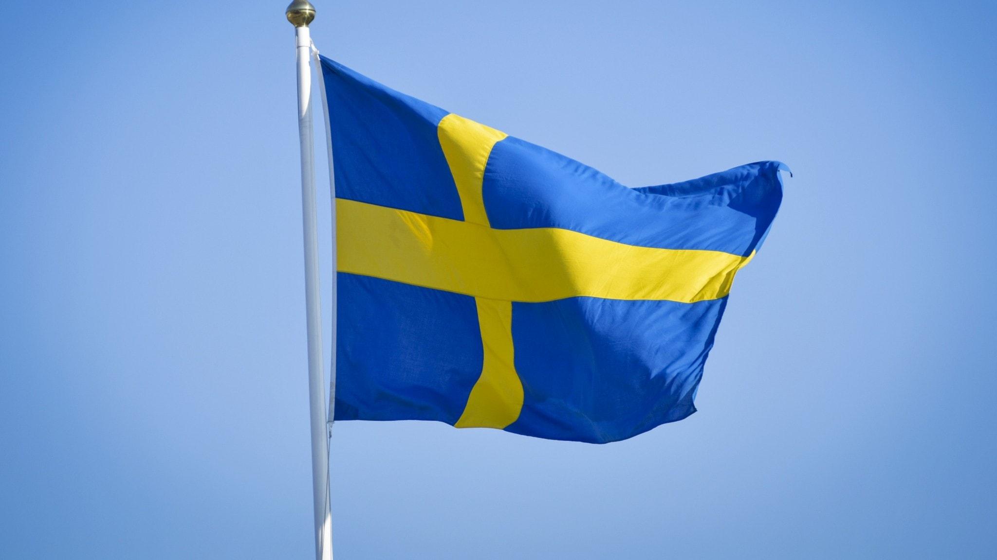 En bild på den svenska flaggan mot en blå himmel.