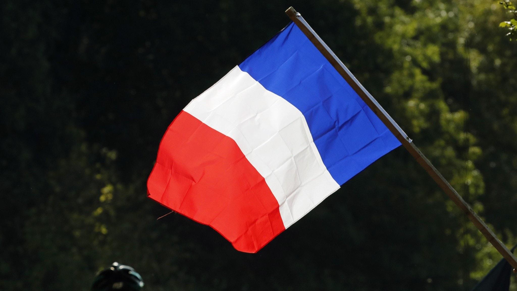 Franska flaggan vajar över en grupp cyklister.