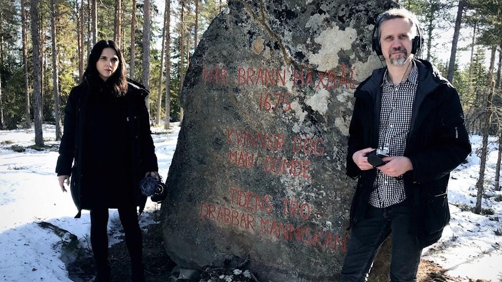 """Moa och Gustav framför minnesstenen på Bålberget. Texten lyder """"Här brann häxbål 1675. Män dömde, kvinnor dog. Tidens tro drabbar människan."""""""