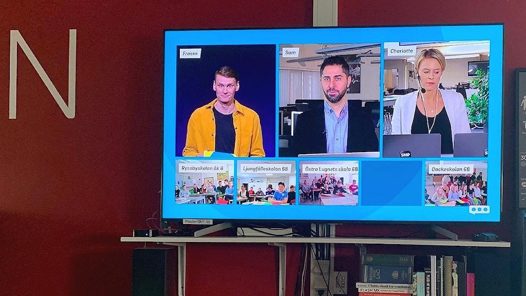 En tv-skärm med programledarna för Fria ordets dag och medverkande skolklasser