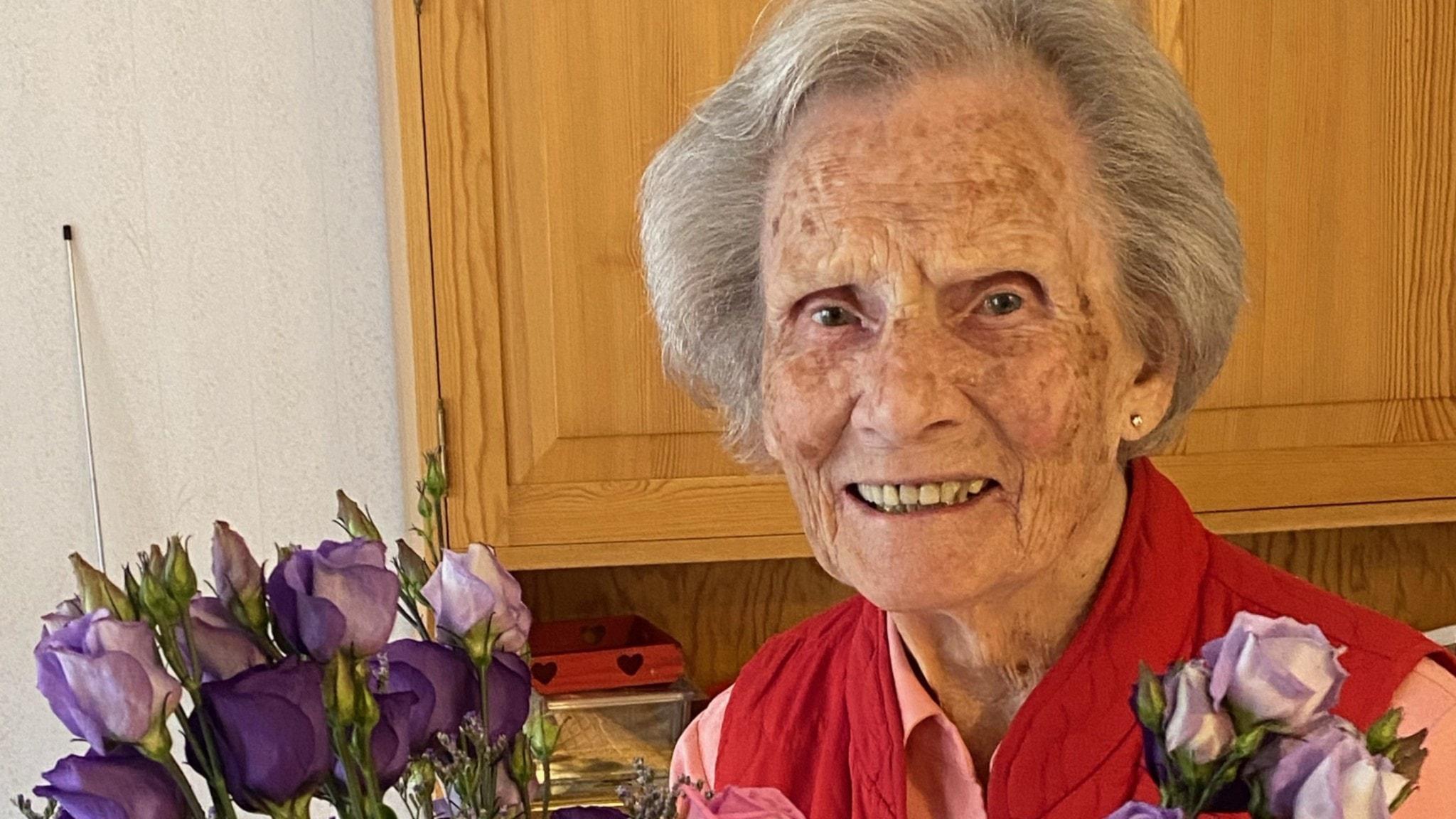 Elly Croneman står i sitt kök med en blombukett
