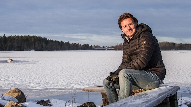 Gerhard Stenlund publikredaktör P4 Västerbotten sitter på en bänk vid älven