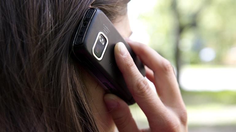En kvinna pratar i en mobiltelefon