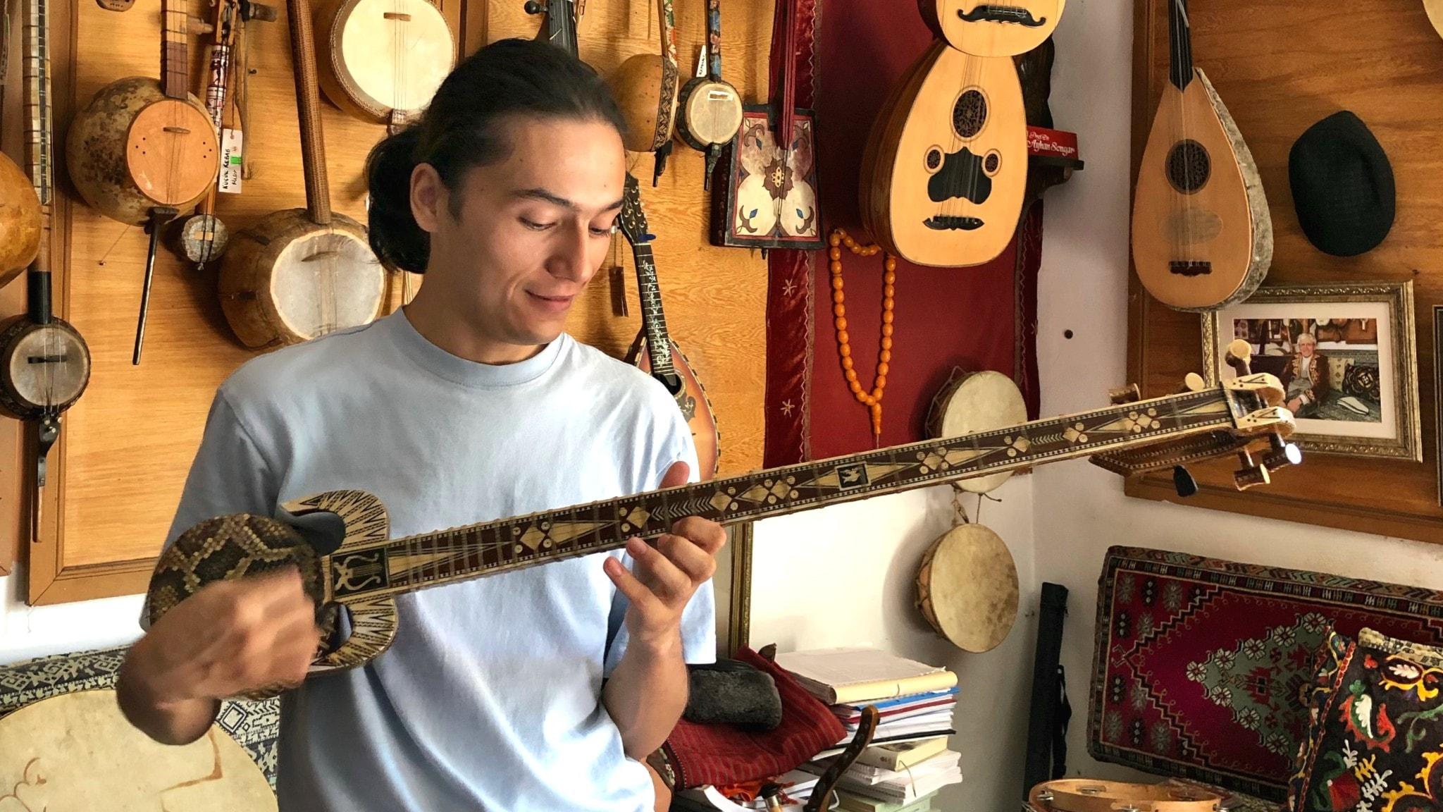"""Shoret Nur spelar ravap, ett uiguriskt stränginstrument, på Muséet för Centralasiatisk musik"""" i Istanbul"""