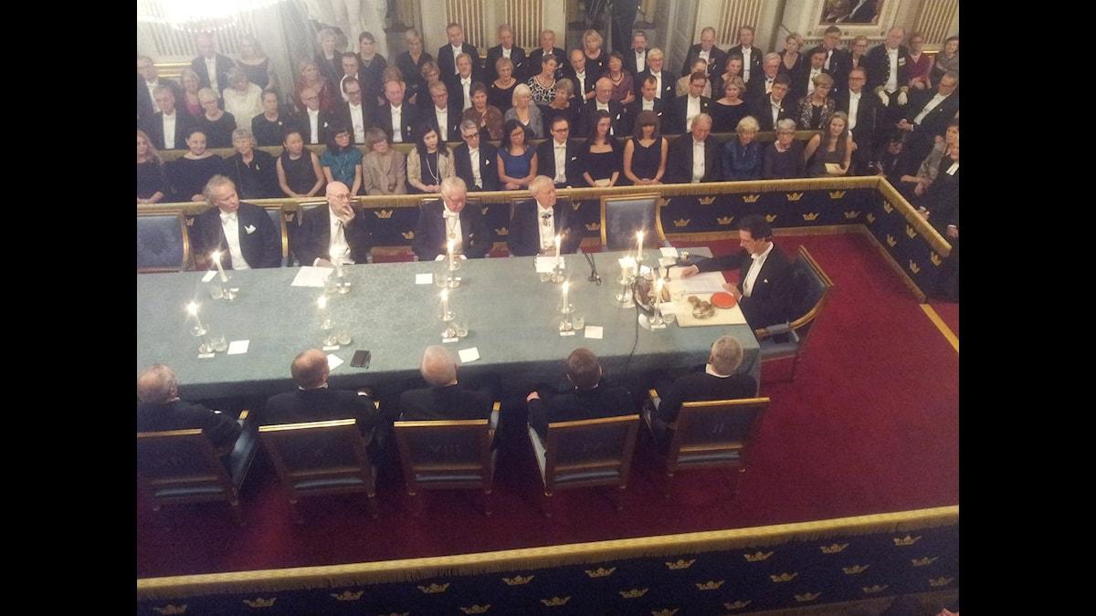 Svenska Akademiens direktörTomas Riad inleder vid höger bordsända.